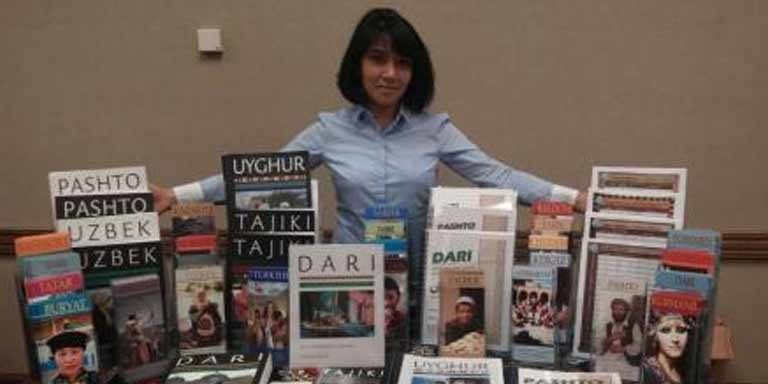 Woman at a table showing off a collection of books and brochures
