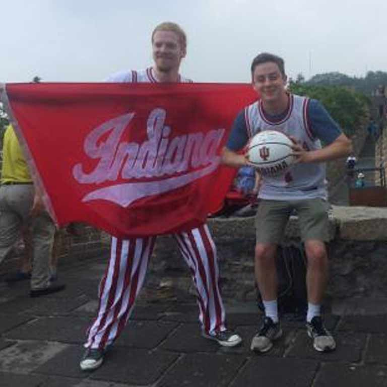 Students abroad holding an Indiana University flag